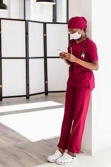 Vrouwelijke arts die op een muur leunt