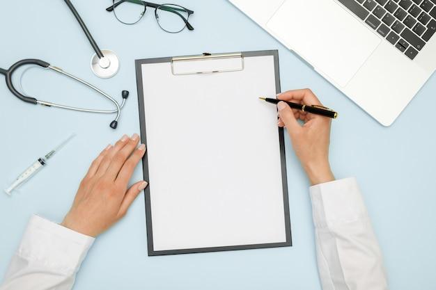 Vrouwelijke arts die op het werk met laptop werkt