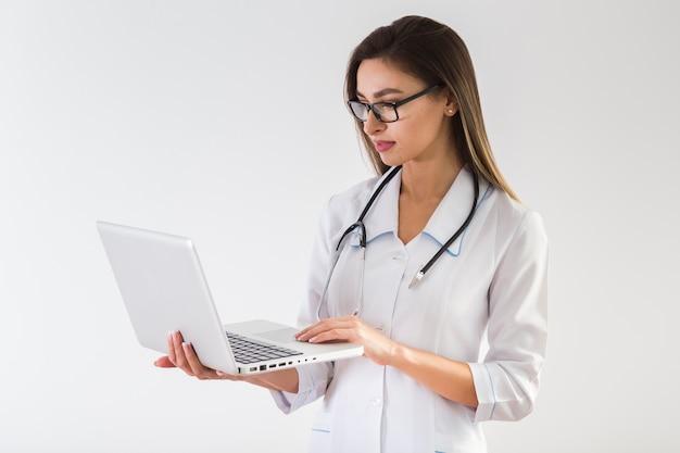 Vrouwelijke arts die op laptop kijkt