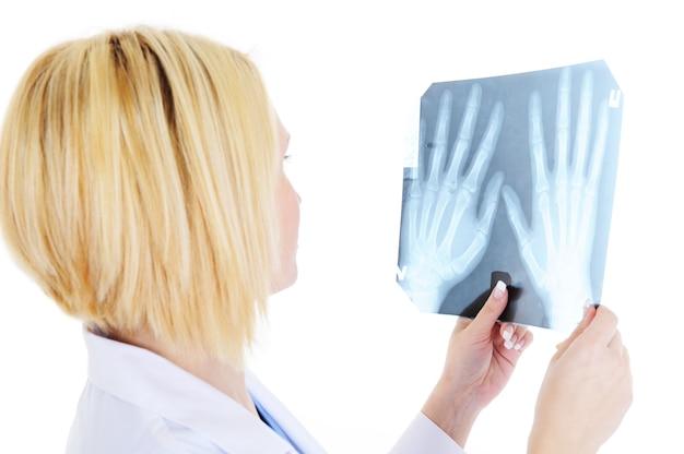 Vrouwelijke arts die op x-ray kijkt - die op wit wordt geïsoleerd