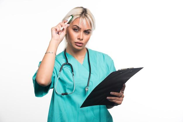 Vrouwelijke arts die over iets denkt terwijl hij klembord op witte achtergrond houdt. hoge kwaliteit foto