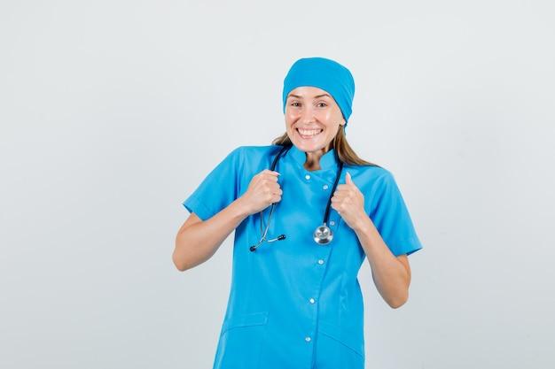 Vrouwelijke arts die overwinning in blauw uniform viert en gelukkig kijkt
