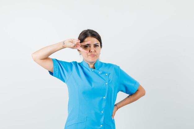 Vrouwelijke arts die overwinningsteken op oog in blauw uniform toont en er zelfverzekerd uitziet