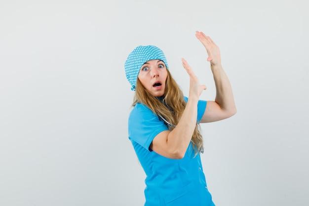 Vrouwelijke arts die palmen opheft om zich in blauw uniform te verdedigen en bang kijkt