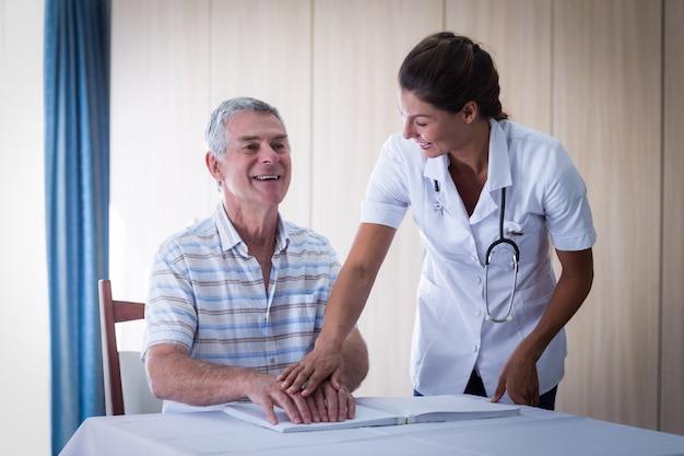 Vrouwelijke arts die patiënt helpt bij het lezen van het brailleboek