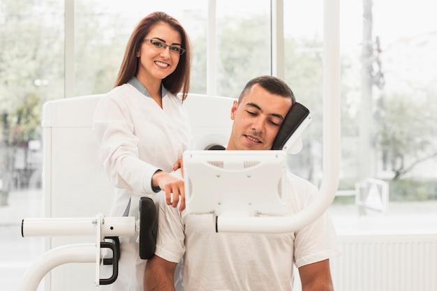 Vrouwelijke arts die patiënt toont hoe te om medische machine te gebruiken