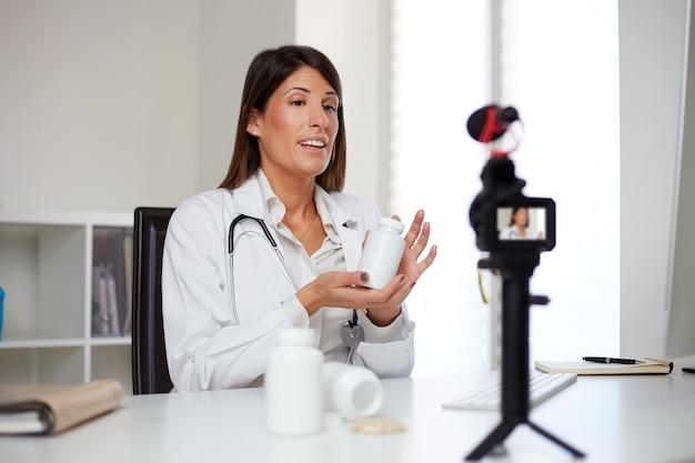 Vrouwelijke arts die pillen toont en een videovlog opneemt