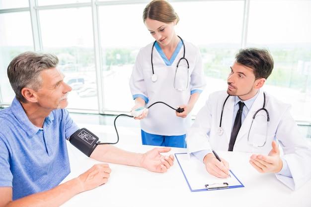 Vrouwelijke arts die rijpe geduldige bloeddruk neemt.