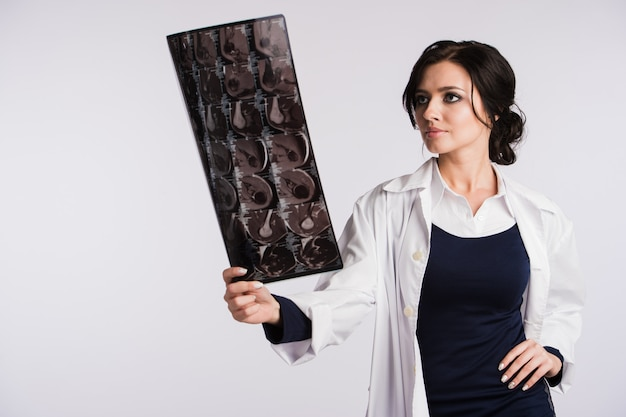 Vrouwelijke arts die röntgenfoto'sröntgenstraal bekijkt