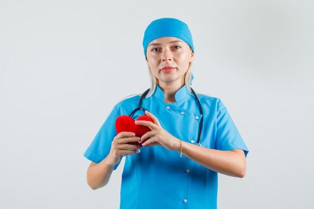 Vrouwelijke arts die rood hart houdt en in blauw uniform glimlacht