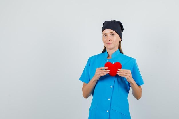 Vrouwelijke arts die rood hart houdt en in blauwe uniforme, zwarte hoed glimlacht