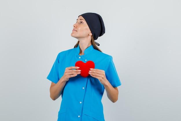 Vrouwelijke arts die rood hart houdt en naar kant kijkt in blauw uniform, zwart hoed vooraanzicht.