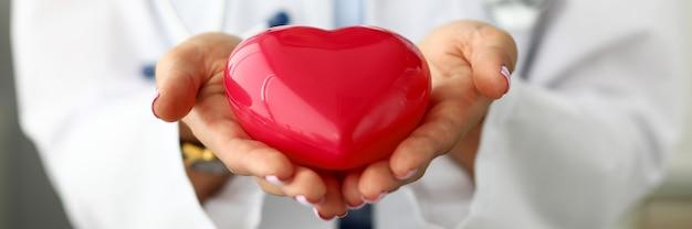 Vrouwelijke arts die rood hart houdt