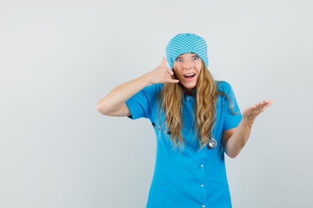Vrouwelijke arts die telefoongebaar in blauw uniform toont en nuttig kijkt
