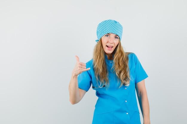 Vrouwelijke arts die telefoongebaar in blauw uniform toont en zelfverzekerd kijkt