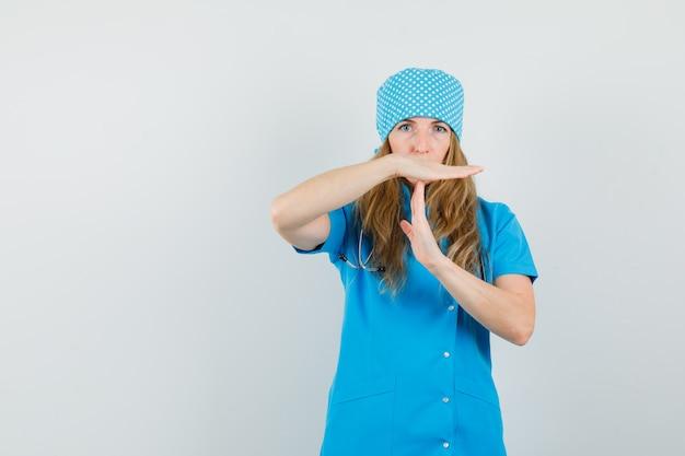 Vrouwelijke arts die tijdonderbrekinggebaar in blauw uniform toont en ernstig kijkt.