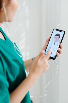 Vrouwelijke arts die toepassing op tabletcomputer gebruikt om haar collega video te bellen