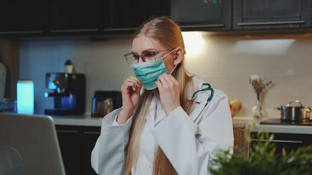 Vrouwelijke arts die toont hoe medisch masker door videogesprek op computer te dragen
