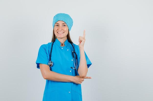 Vrouwelijke arts die vinger in blauw uniform benadrukt en vrolijk kijkt. vooraanzicht.