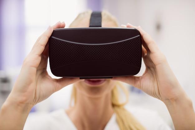 Vrouwelijke arts die virtuele werkelijkheidshoofdtelefoon draagt