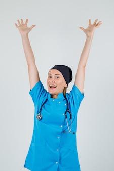 Vrouwelijke arts die wapens in uniform opheft en gelukkig kijkt. vooraanzicht.