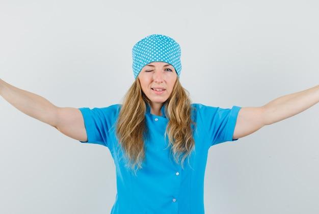 Vrouwelijke arts die wapens spreidt en oog knipogen in blauw uniform