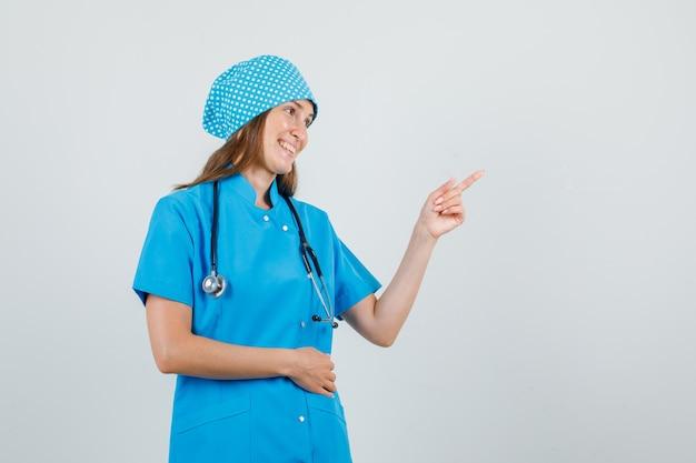 Vrouwelijke arts die weg wijst en opzij kijkt in blauw uniform en er vrolijk uitziet