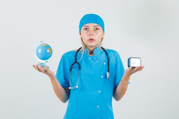 Vrouwelijke arts die wereldbol en klok in blauw uniform houdt en ernstig kijkt