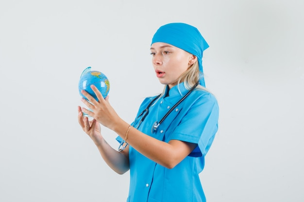 Vrouwelijke arts die wereldbol in blauw uniform houdt en verbaasd kijkt
