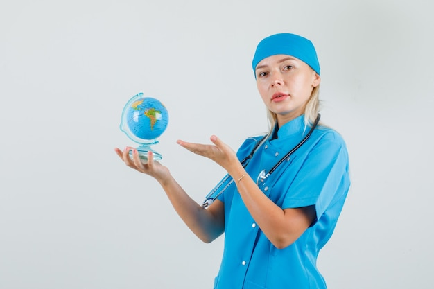 Vrouwelijke arts die wereldbol in blauw uniform toont en voorzichtig kijkt.