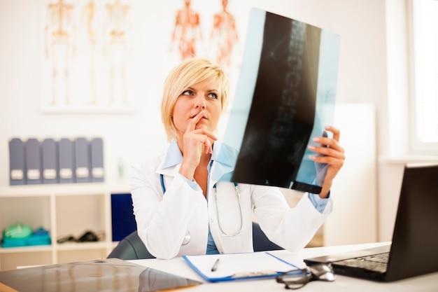 Vrouwelijke arts die wervelkolomröntgenstraal bestudeert