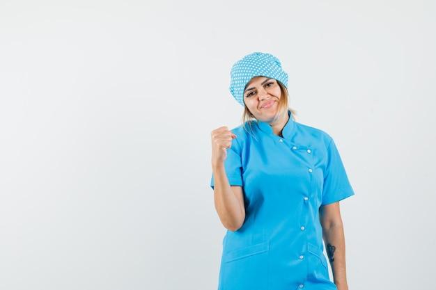 Vrouwelijke arts die winnaargebaar in blauw uniform toont en er gelukkig uitziet