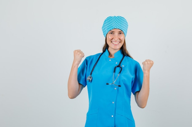 Vrouwelijke arts die winnaargebaar in blauw uniform toont en vrolijk kijkt