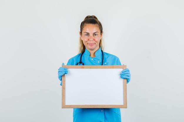 Vrouwelijke arts die wit bord houdt en in blauw uniform glimlacht