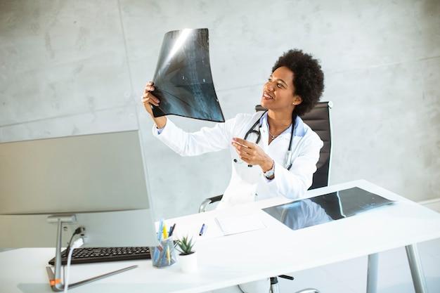 Vrouwelijke arts die witte jas met een stethoscoop draagt die achter bureau in het bureau zit en x-ray beeld kijkt