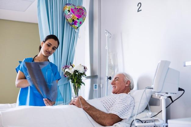 Vrouwelijke arts die x-ray rapport bespreken met mannelijke hogere patiënt in de afdeling