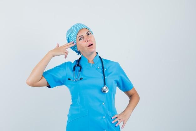 Vrouwelijke arts die zelfmoordgebaar in blauw uniform imiteert en er zelfverzekerd uitziet. vooraanzicht.