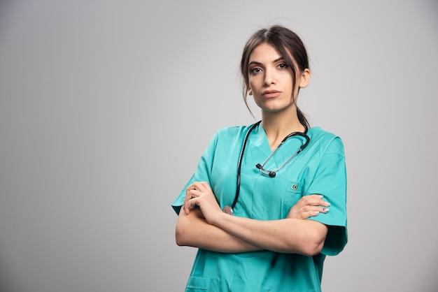 Vrouwelijke arts die zich op grijs bevindt