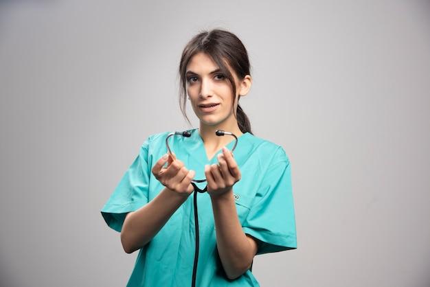 Vrouwelijke arts die zich voordeed op grijs