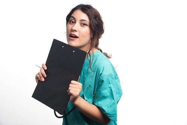 Vrouwelijke arts die zwart klembord in handen op witte achtergrond houdt. hoge kwaliteit foto