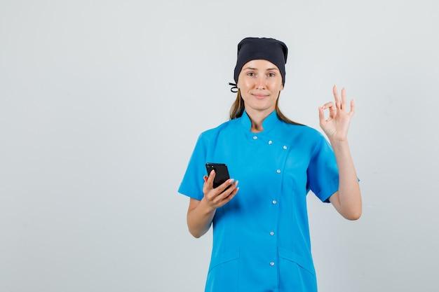 Vrouwelijke arts doet ok teken met smartphone in blauw uniform, zwarte hoed en kijkt tevreden. vooraanzicht.