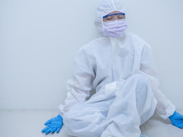Vrouwelijke arts dragen van beschermende pak leunt achterover en rust