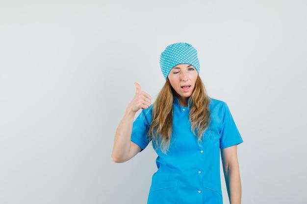 Vrouwelijke arts duim opdagen en oog in blauw uniform knipogen