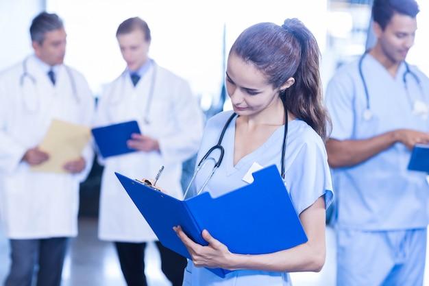 Vrouwelijke arts een medisch rapport schrijven en collega's die zich erachter bevinden