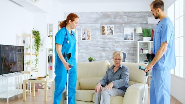 Vrouwelijke arts en haar assistent helpen oude vrouw met krukken om op te staan van de bank en een wandeling te maken