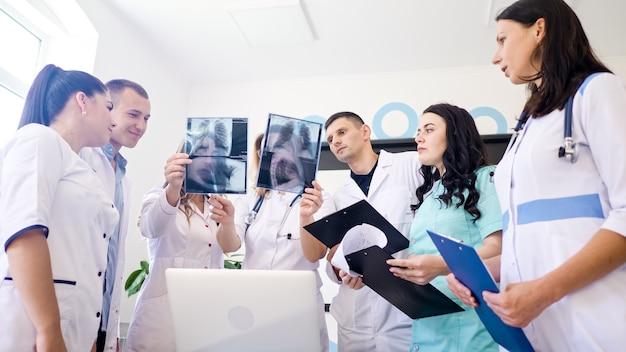 Vrouwelijke arts en jonge medische stagiaires in medische kleding die samen de resultaten van de thoraxfoto bestuderen...