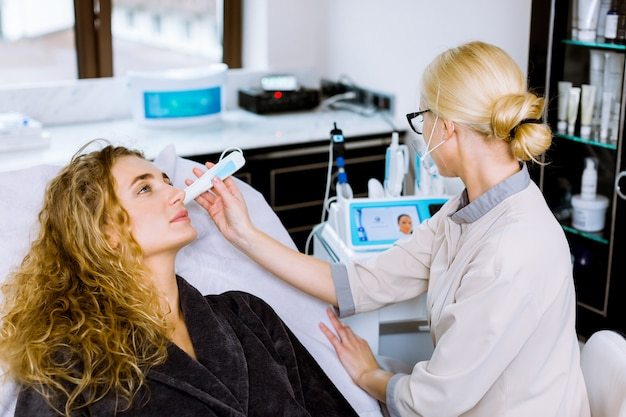 Vrouwelijke arts en patiënt tijdens onderzoek van de gezichtshuid. resultaten van de huidaandoening worden op het display weergegeven.