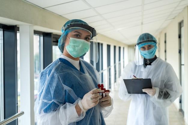 Vrouwelijke arts en verpleegster in persoonlijke beschermende kleding bespreken over de patiënt van de resultaattest