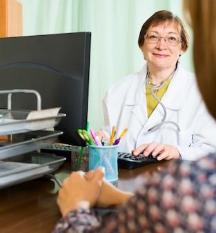 Vrouwelijke arts en vrouw bespreken iets