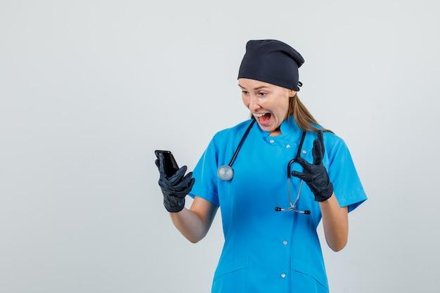 Vrouwelijke arts gebaren tijdens het kijken naar smartphone in uniform, handschoenen en op zoek gelukkig. vooraanzicht.